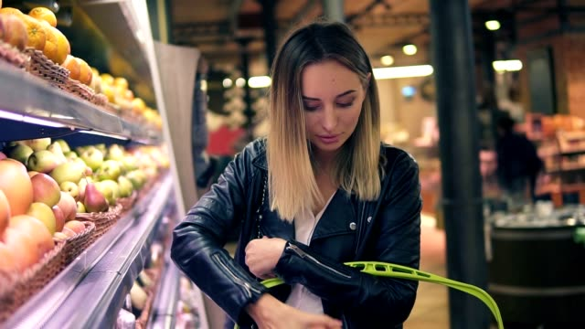 sale, food, shopping, consumerism and people concept. blonde woman choosing fruits from the colourful shelves in supermarket. side view - cestino video stock e b–roll