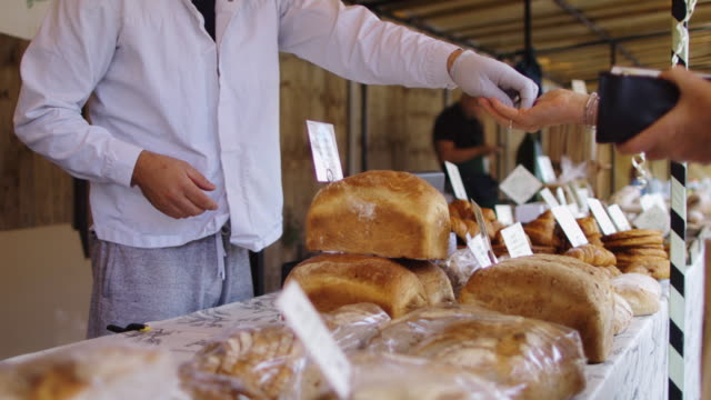 Sale on Bread Stall at Farmers Market A baker hands change over to a customer, selling bread at a farmers market. bread stock videos & royalty-free footage