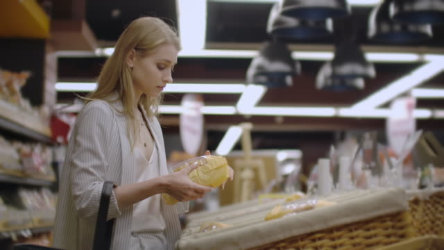sale, shopping, consumerism and people concept - happy young woman choosing and reading label on bread in market. - pane forno video stock e b–roll