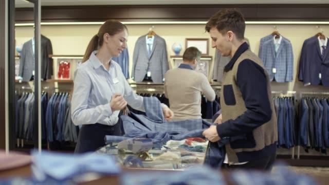 sales assistant advising man buying suit - ассистент стоковые видео и кадры b-roll