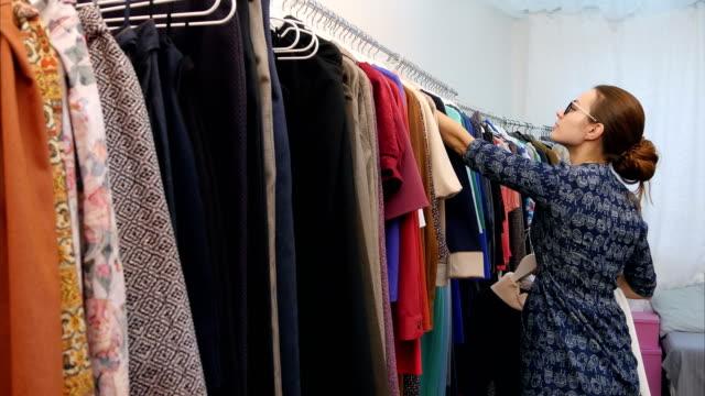 Vendeuse en fixation armoire de vêtements magasin - Vidéo