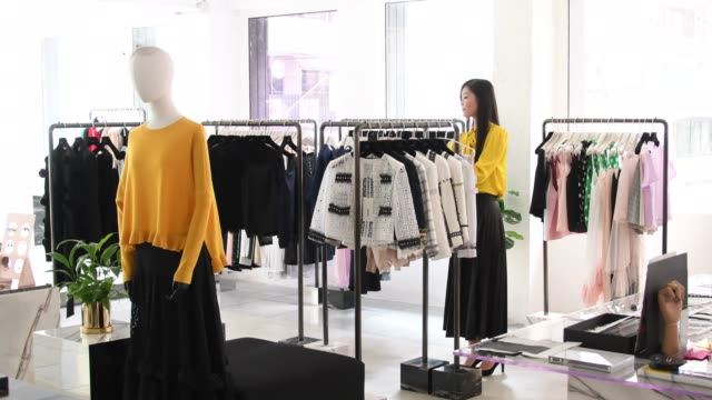 Sales assistant ordering new jackets on clothes rail Mid adult Chinese woman working in fashion department store, new clothes hanging on railings, efficiency, organisation, retail department store stock videos & royalty-free footage
