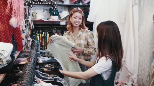 リサイクルショップでヴィンテージ衣料品を買い物している若い女性客を手伝う店員 - オペレーター 日本人点の映像素材/bロール