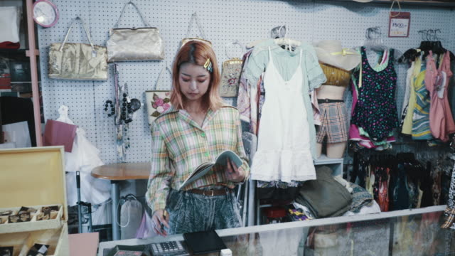 Sales clerk standing behind the register in a thrift store Sales clerk standing behind the register in a thrift store in Japan small business saturday stock videos & royalty-free footage