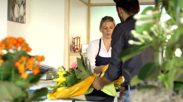 Sales manager at counter and client shopping in flowers shop video