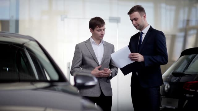 Sales manager convincing a customer to buy a car