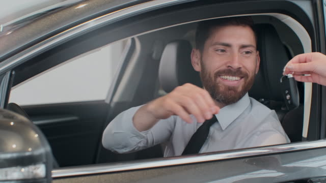 Sales manager handing over the keys to man that sitting in the car. Sales manager handing over the keys to man that sitting in the ca. car key stock videos & royalty-free footage