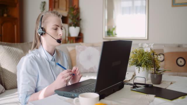 sales representative in headset speaking to client and making video conference call on laptop. - praca w sektorze handlowym filmów i materiałów b-roll
