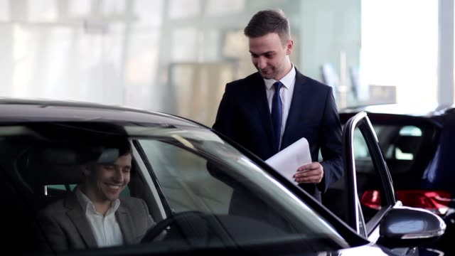 Salesman assuring buyer in selection of this car
