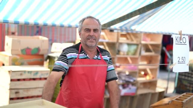 salesman at farmer's market - video di bancarella video stock e b–roll