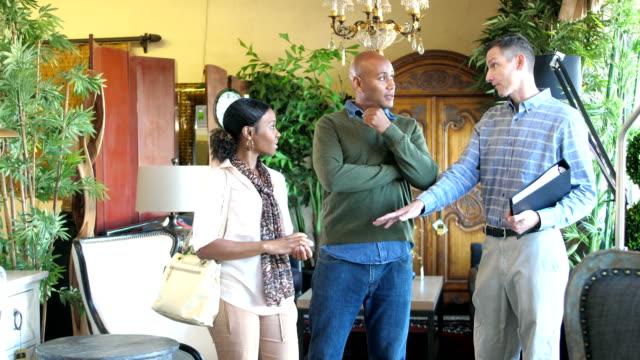 vídeos de stock, filmes e b-roll de vendedor ajudar casal africano-americano comprar móveis - mobília