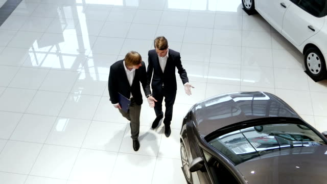 Salesman helping customer to choose a car Salesman helping customer to choose a car. Handsome salesman assisting client in car dealership. Sales manager convinces a customer to buy this car. Salesman talking with client in car dealership. car salesperson stock videos & royalty-free footage
