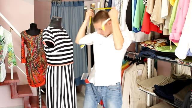 vídeos de stock, filmes e b-roll de vendedor em boutique é um manequim para se vestir. - tag