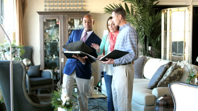 Salesman in furniture store helping couple A mature African-American man in his 40s working in a furniture store helping a couple look through catalogs. interior designer stock videos & royalty-free footage