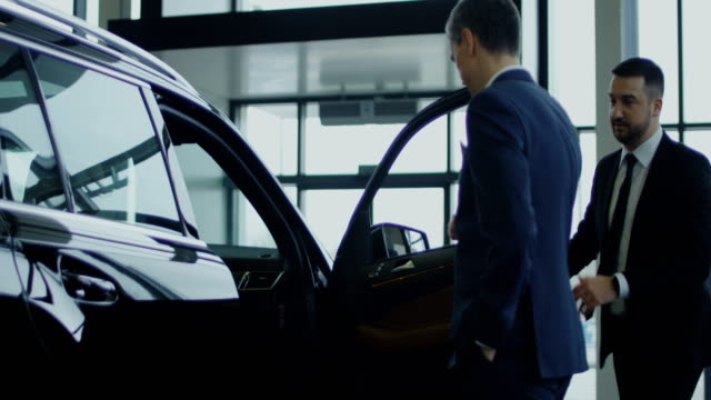 Salesman inviting potential buyer to get in car Elegant salesman inviting potential buyer to get in the car in showroom. Slow motion. Shot on Red cinema camera. car salesperson stock videos & royalty-free footage