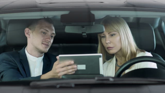 Salesman make a deal of buying car and woman signs electronic contract in cabin video