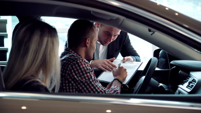 Salesman negotiating a contract with customers Salesman negotiating a contract with customers purchasing a new car leaning through the window with the paperwork car shopping stock videos & royalty-free footage