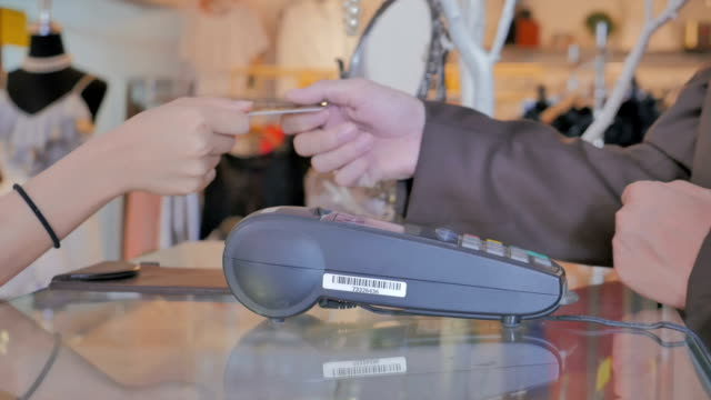 Salesman swiping credit card through credit card reader in boutique video