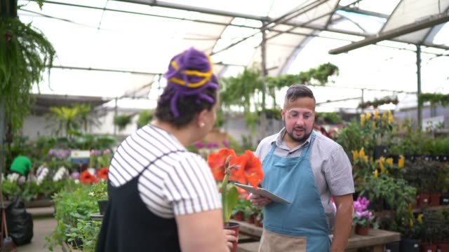Salesman using digital tablet and helping customer buying flowers