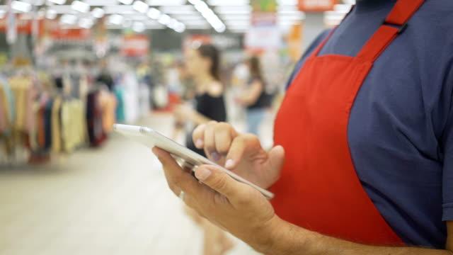 Salesman using digital tablet in supermarket Male Holding Digital Tablet In supermarket salesman stock videos & royalty-free footage