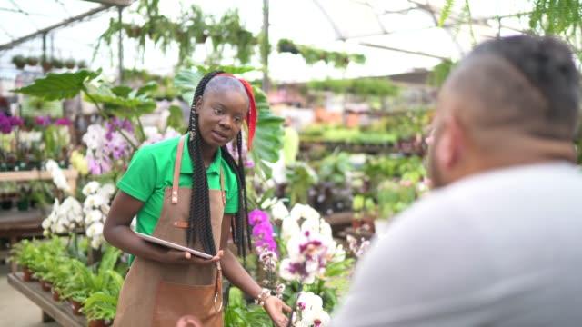 Saleswoman helping customer choosing flowers