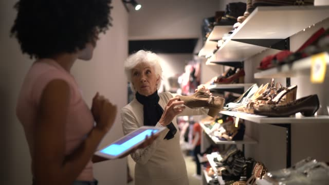 Saleswoman helping senior woman shopping for shoes