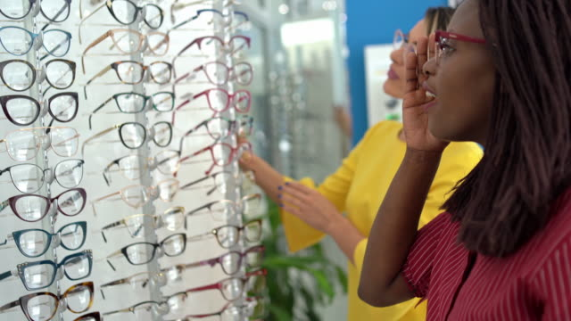 Saleswoman Helps Beautiful Young Woman Choose Glasses Saleswoman helps beautiful young woman to choose glasses. eye exam stock videos & royalty-free footage