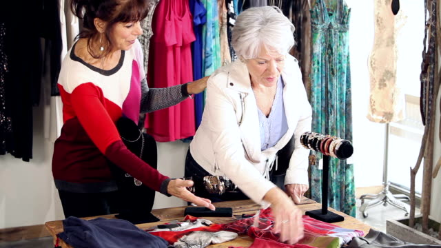 Saleswoman in clothing store helps customer A saleswoman in a clothing store helping a customer who is looking at the selection of merchandise on a table. saleswoman stock videos & royalty-free footage