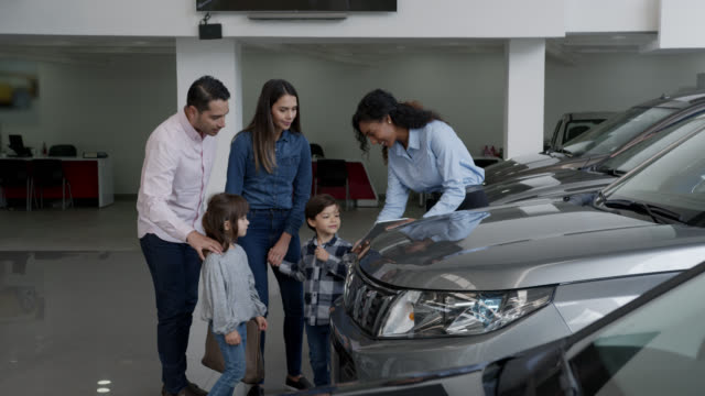 Saleswoman showing specifics of a car to a Latin American family at the dealership using a tablet computer after choosing a car