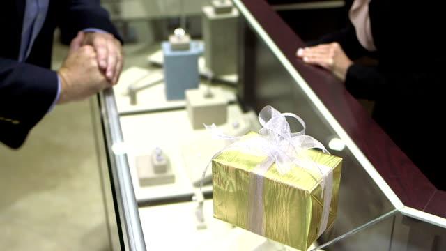 stockvideo's en b-roll-footage met verkoopster toont ringen aan de mens in juwelier - ring juweel