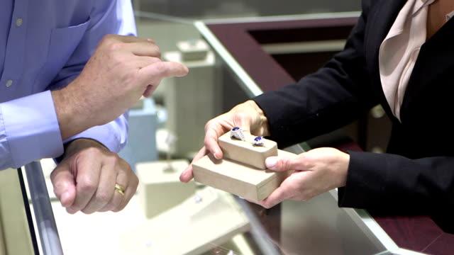 vidéos et rushes de vendeuse montre des anneaux à l'homme dans la boutique de bijoux - joaillerie