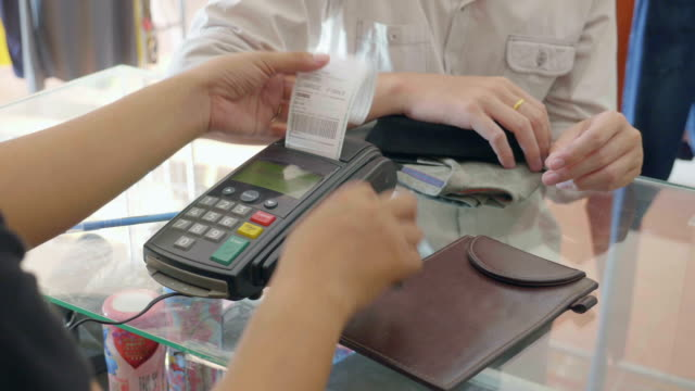 expediten att svepa kreditkort via kreditkort reader i boutique - spendera pengar bildbanksvideor och videomaterial från bakom kulisserna