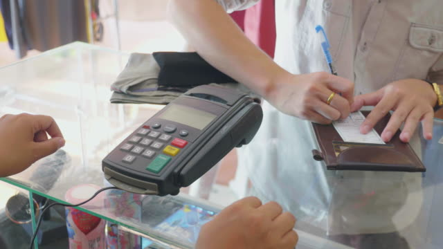 vidéos et rushes de vendeuse interactions carte de crédit au lecteur de carte de crédit dans la boutique - relation client