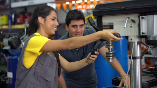 Saleswoman teaching a customer how to use a machine tool both smiling video