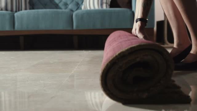 saleswoman unfolding the carpet - tappeto video stock e b–roll