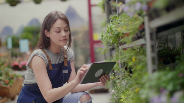 Saleswoman using digital tablet while examining plants on rack video