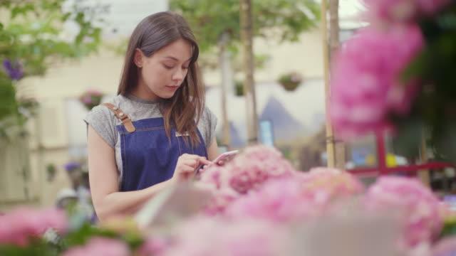 Saleswoman using smartphone while examining hydrangea flowers video
