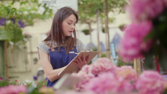 Saleswoman writing on clipboard while counting flowers in shop video