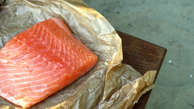 Salmon fillet on the table with cooking utensils. video
