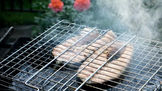 lax rödfisk på en grill. grillning öring biffar. matlagning rostad fisk på öppen eld. grill, utomhus. village livsstil. rå öring biff matlagning. vackra skytte av mat - marinad bildbanksvideor och videomaterial från bakom kulisserna