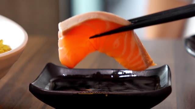 Salmon sashimi dipping with soy sauce Salmon sashimi dipping with soy sauce sashimi stock videos & royalty-free footage