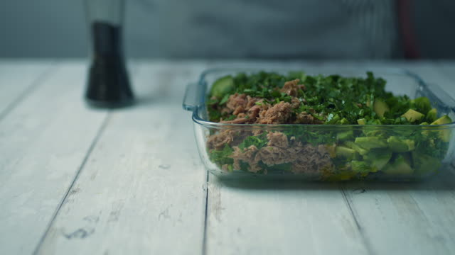 vídeos de stock, filmes e b-roll de salgando uma salada de atum e abacate em uma tigela de vidro com pepino, cebola vermelha, suco de limão, coentro, pimenta preta, azeite. - comida salgada