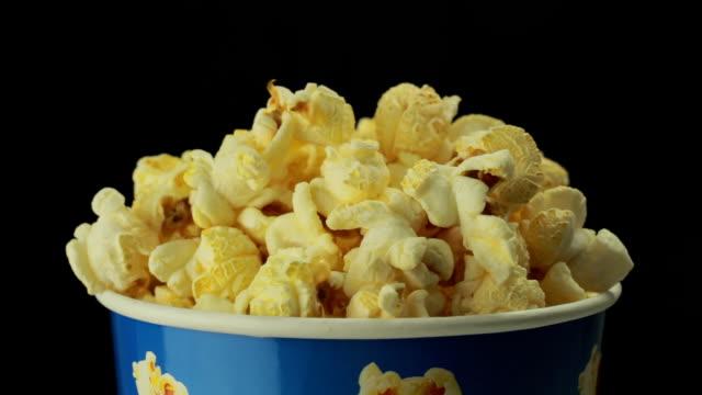 Salty popcorn slowly rotates on black background video
