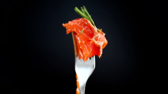salty red fish on a fork, black background video