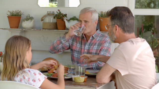 Same Sex Family At Home Eating Meal On Outdoor Verandah video
