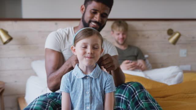 vídeos de stock, filmes e b-roll de pares masculinos do mesmo sexo em casa que começ a filha pronta para a escola que plaiting seu cabelo - homossexualidade