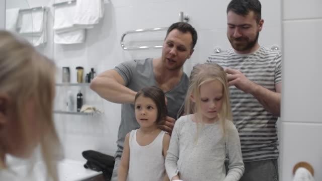 1 однополые пары делают daughtersâ незамедлительно волос - один родитель стоковые видео и кадры b-roll