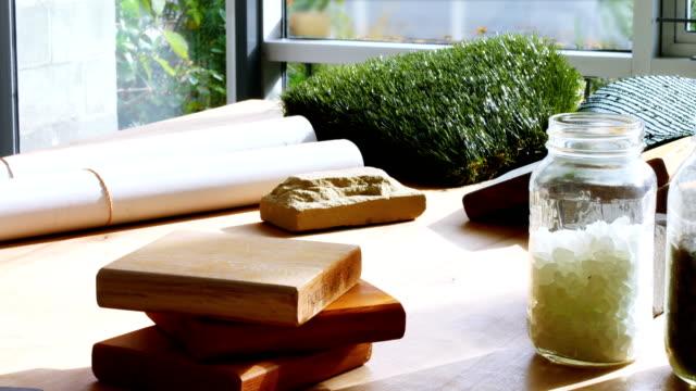 vidéos et rushes de échantillon de cailloux dans le bocal, dalle, blueprint et gazon artificiel sur table - pots de bureau