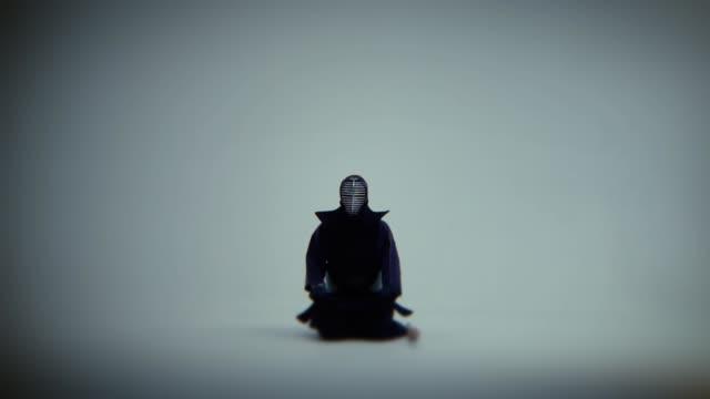 サムライ剣道は白い部屋に座って瞑想します。ショットのズームを閉じる中 - 武道点の映像素材/bロール