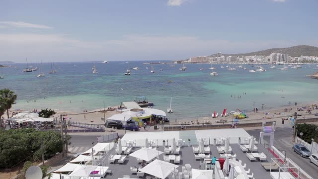 san antonio bay ibiza beach, aerial view, panoramic view of the city of ibiza, beaches, pigeons flying and cars passing - formaggio comté video stock e b–roll